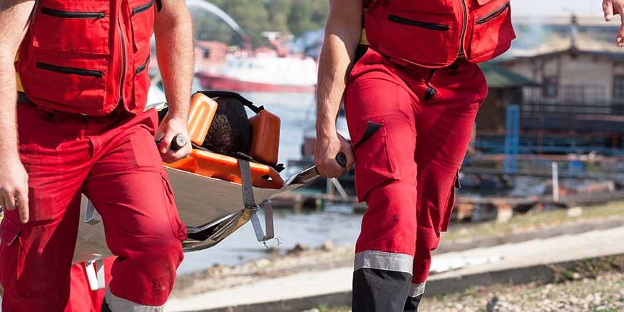 Rettungskräfte tragen verletzte Person auf einer Trage