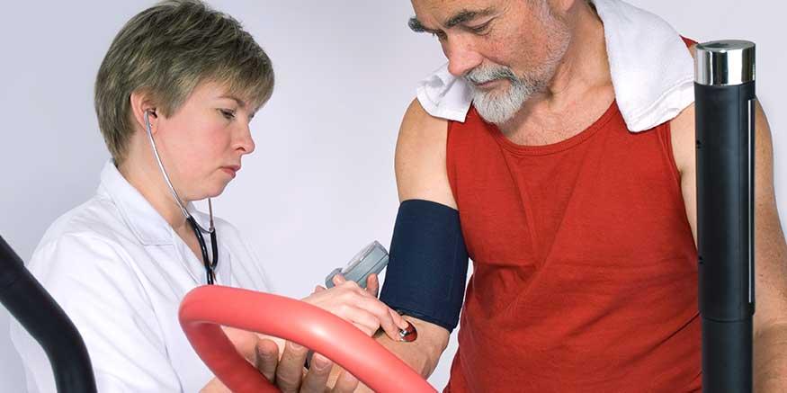 Ärztin misst Blutdruck eines Mannes
