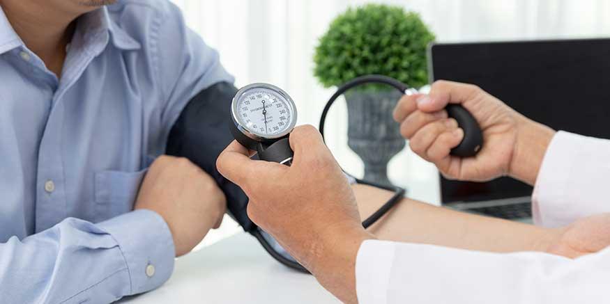 Arzt misst Blutdruck einer Person