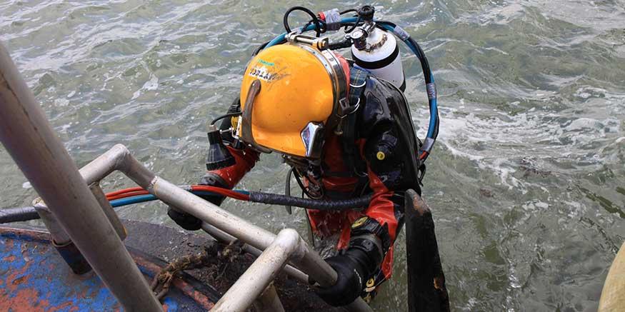 Taucher in Schutzausrüstung steigt aus Wasser