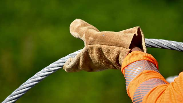 Hand in Festmacherhandschuh hält Seil