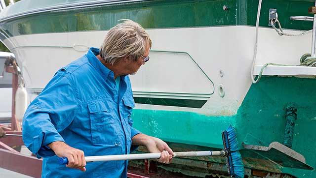 Mann reinigt Außenwand eines Bootes mit einem Besen