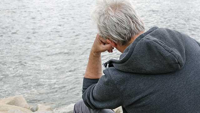 Mann blickt sorgenvoll auf Wasser