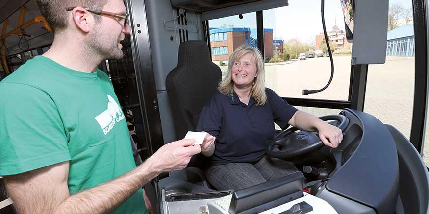 Busfahrerin überreicht Fahrgast ein Ticket