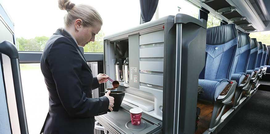 Reiseleiterin bereitet Kaffee im Reisebus zu