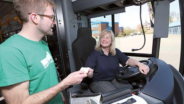 Busfahrerin übergibt Fahrschein an Fahrgast