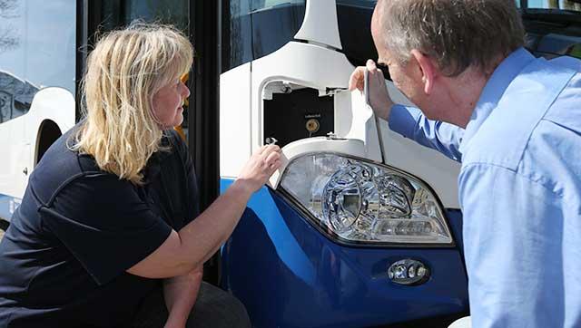 Busfahrerin und Fachkraft für Arbeitssicherheit überprüfen Bus