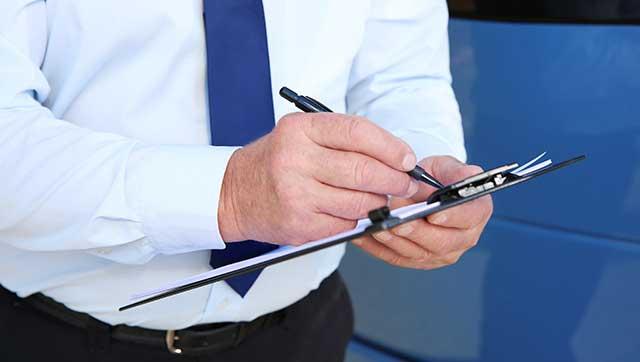 Mann mit Krawatte füllt Checkliste aus