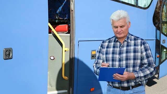 Busfahrer überprüft Liste