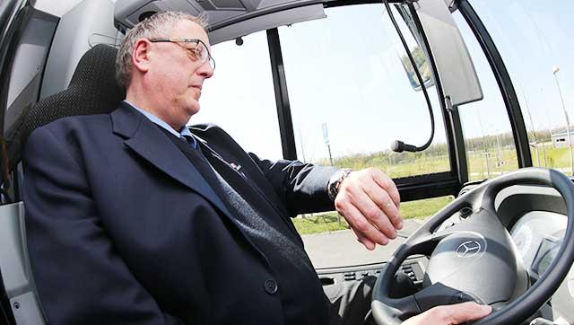 Busfahrer schaut auf seine Armbanduhr