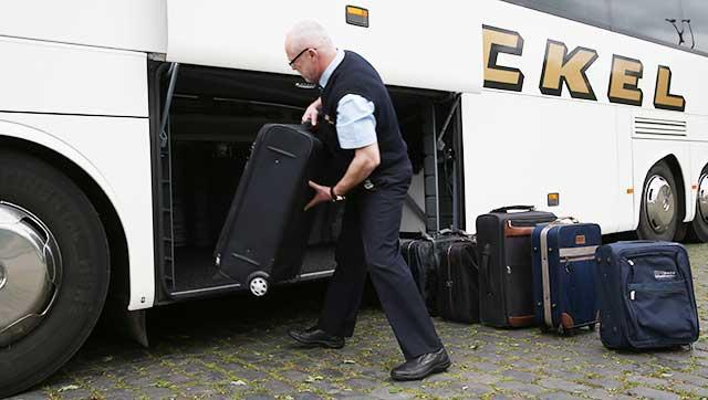 Busfahrer hebt Koffer in Ladeluke