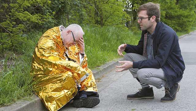 Mann redet beruhigend auf Person mit Rettungsdecke ein