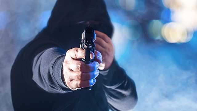 Vermummte Person zielt mit Pistole