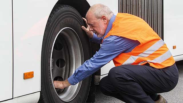Busfahrer prüft Reifen
