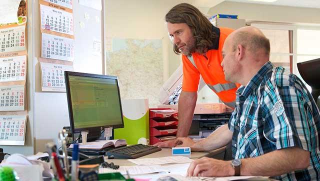 zwei Männer schauen auf einen Monitor