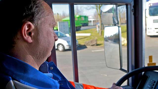 Fahrer eines Entsorgungsfahrzeugs schaut in Seitenspiegel
