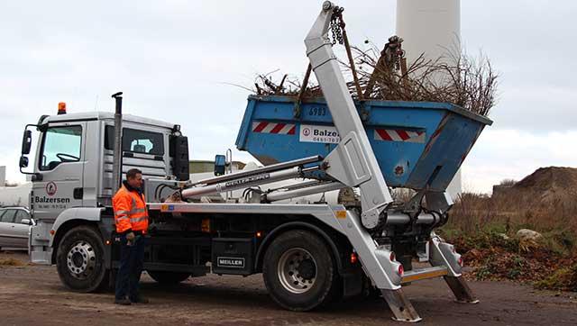 Container mit Baumbeschnitt wird abgekippt