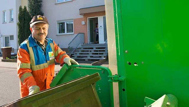 Müllwerker in PSA hält Mülltonne fest