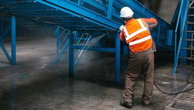 Mann reinigt Förderband mit Hochdruckwasserstrahl