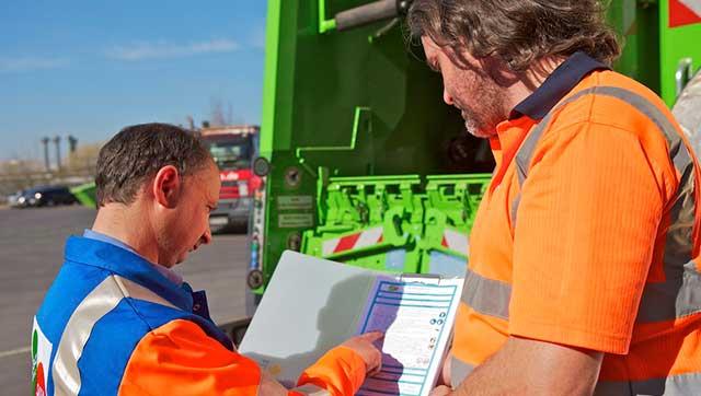Zwei Männer in Arbeitskleidung schauen auf Checkliste