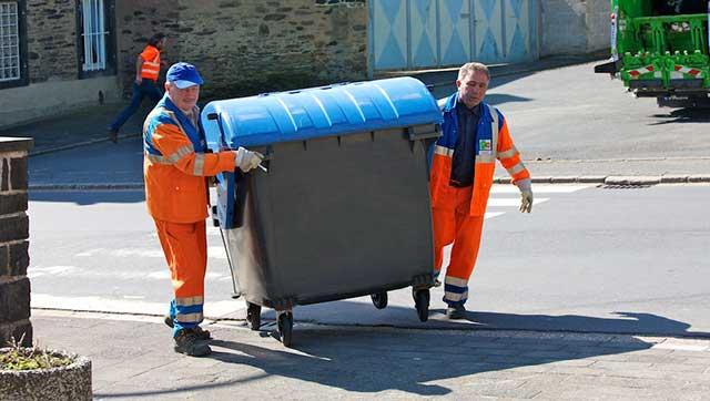 Müllwerken schieben Tonne