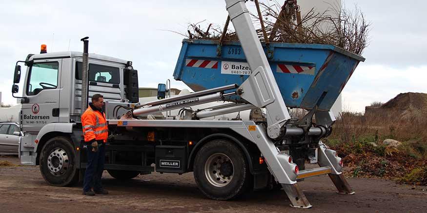 Container mit Baumschnitt wird abgekippt