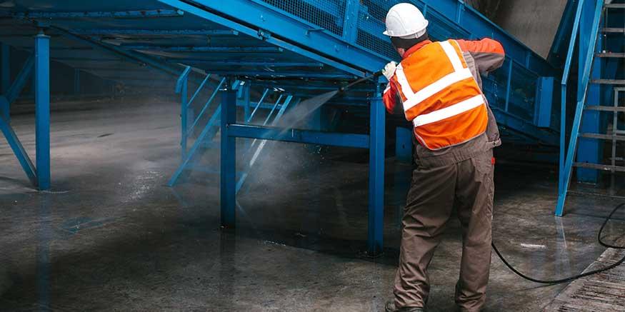 Mitarbeiter reinigt Förderband mit Hochdruckwasser