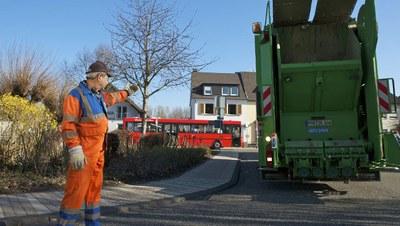 Rückwärtsfahrendes Abfallsammelfahrzeug mit Einweiser