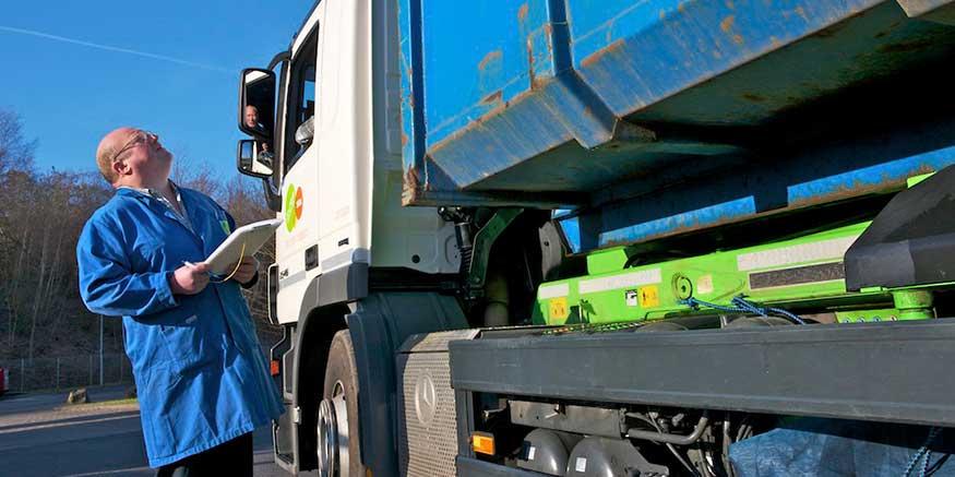 Mann mit Klemmbrett prüft Entsorgungsfahrzeug