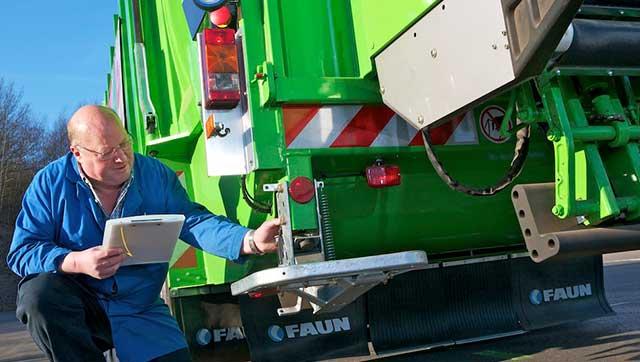 Mann mit Klemmbrett prüft Trittbrett am Entsorgungsfahrzeug