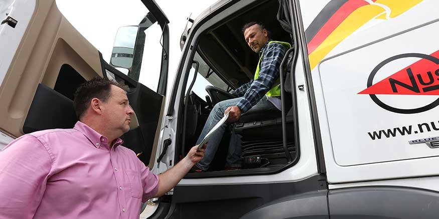 Chef überreicht Lkw-Fahrer Unterlagen