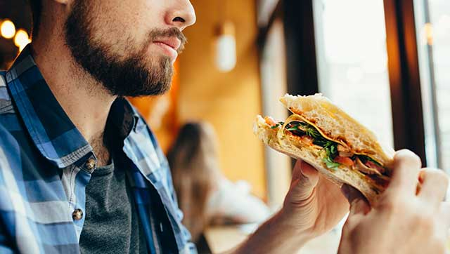 Mann hält Sandwich in der Hand