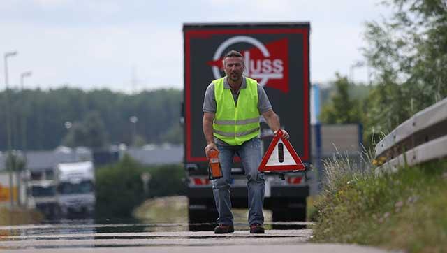 Lkw-Fahrer stellt Warndreieck auf