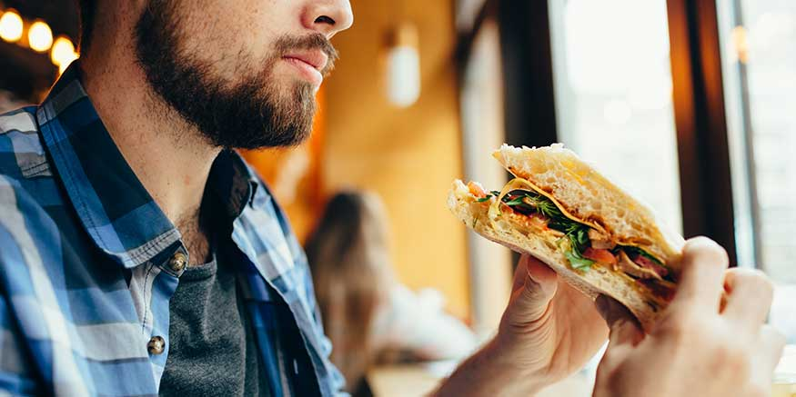 Mann isst Sandwich