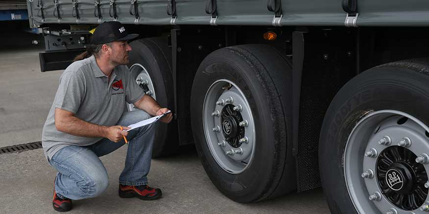 Fahrer kontrolliert Lkw-Reifen