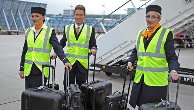 Flugbegleiter und Flugbegleiterinnen mit Warnwesten