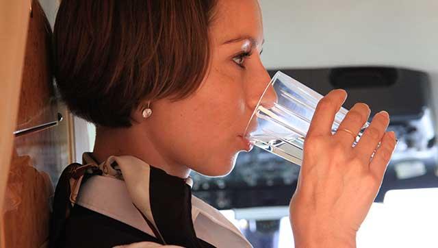 Flugbegleiterin trinkt Wasser in Flugzeug-Kabine