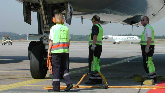 Beschäftigte mit Gehörschutz auf Flughafen-Vorfeld