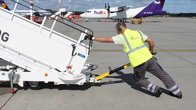 Flughafenmitarbeiter schiebt Gangway