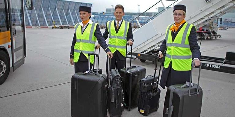 Flugbegleiterinnen und -begleiter mit Warnwesten auf dem Vorfeld