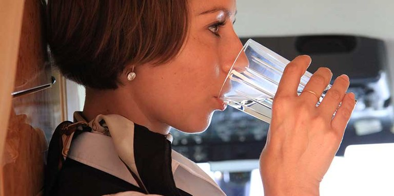 Flugbegleiterin trinkt ein Glas Wasser