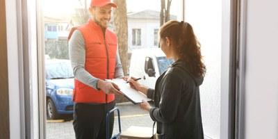 Paketkurier liefert Sendung an Haustür ab
