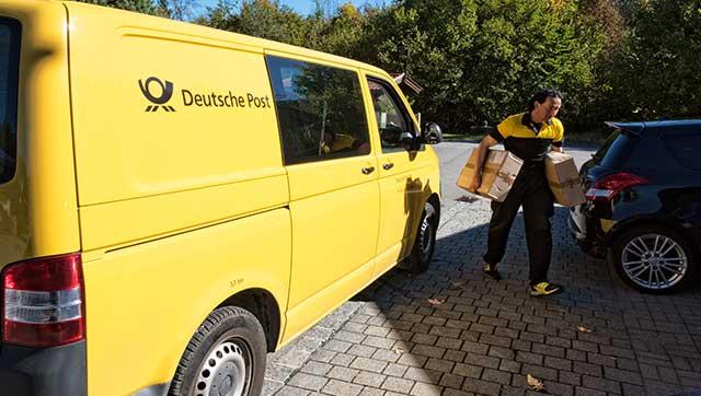 Postbote liefert Pakete mit Pkw aus