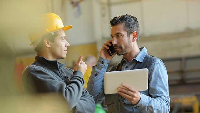 Zwei Männer mit Tablet und Telefon im Gespräch
