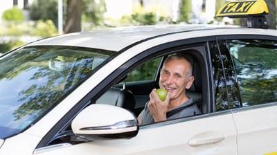 Taxifahrer am Steuer mit Apfel