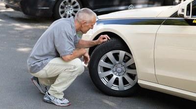 Sicherheitsscheck: Taxifahrer prüft vor der Fahrt das Reifenprofil
