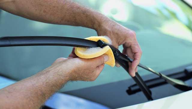 Taxifahrer reinigt Scheibenwischer