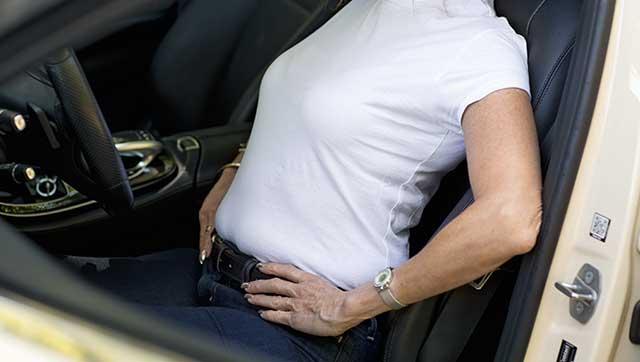 Taxifahrerin macht Rückenübung im Taxi