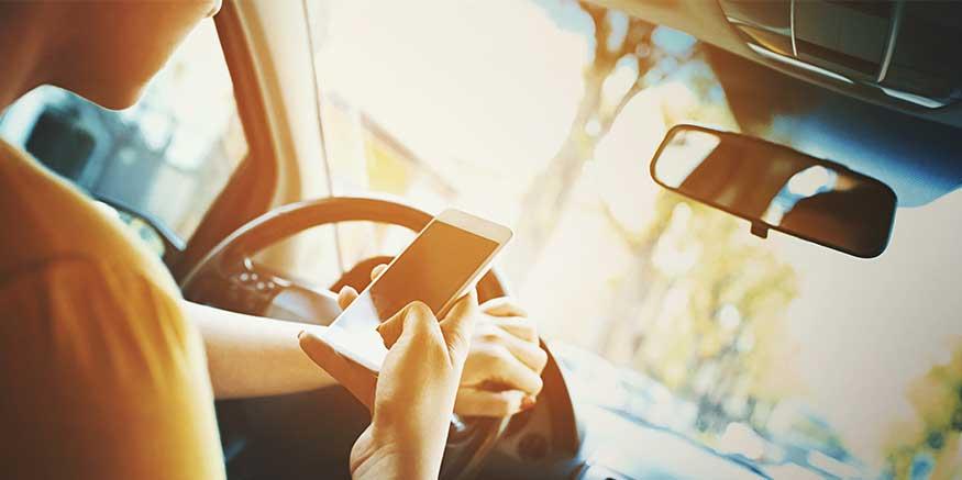 Person sitzt am Steuer und blickt auf Mobiltelefon