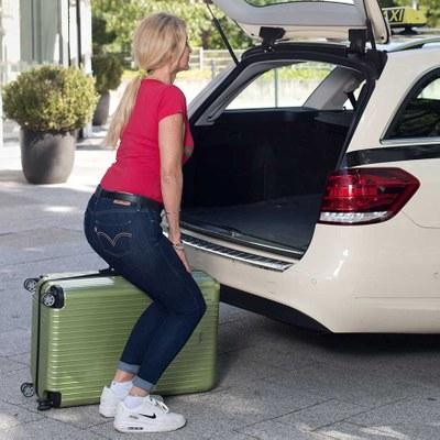 Taxifahrerin geht beim Anheben eines Koffers in die Knie